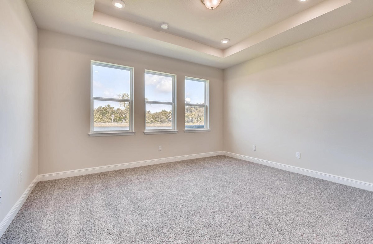 Bayview quick move-in Master bedroom with tray ceiling and pond views
