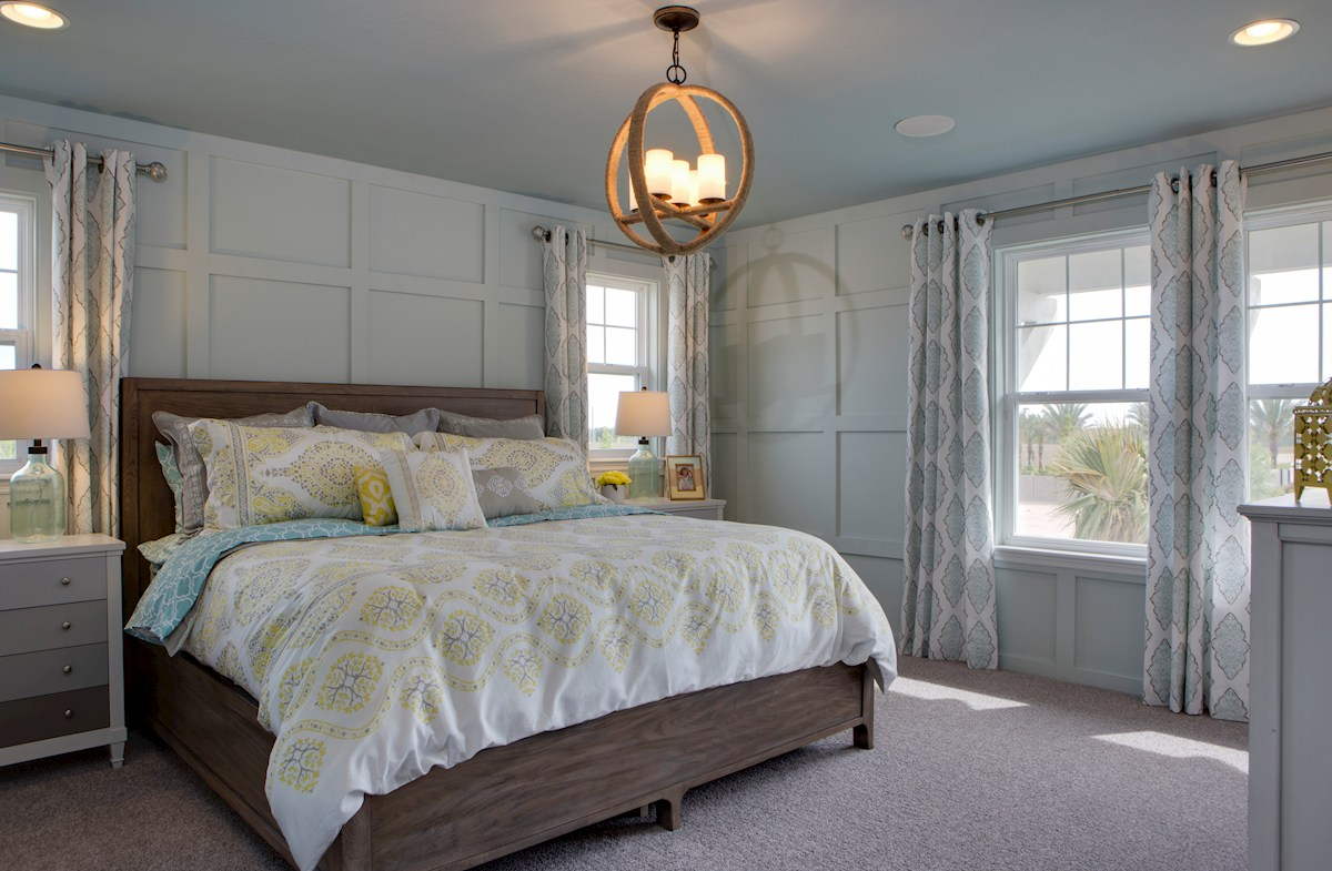 Long Lake Ranch Townhomes Erie Furnished master bedroom with chandelier