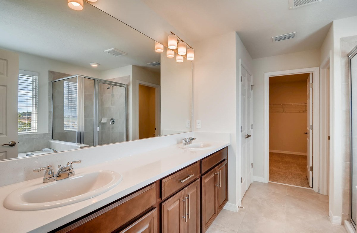 The Reserve at Pradera Sanibel Master bathroom with dual sink vanity and glass enclosed shower