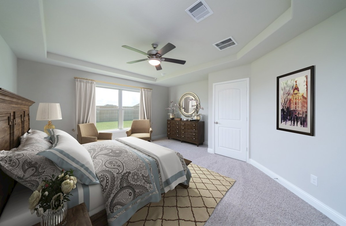 Southwinds Brook master bedroom with ceiling fan and carpet flooring