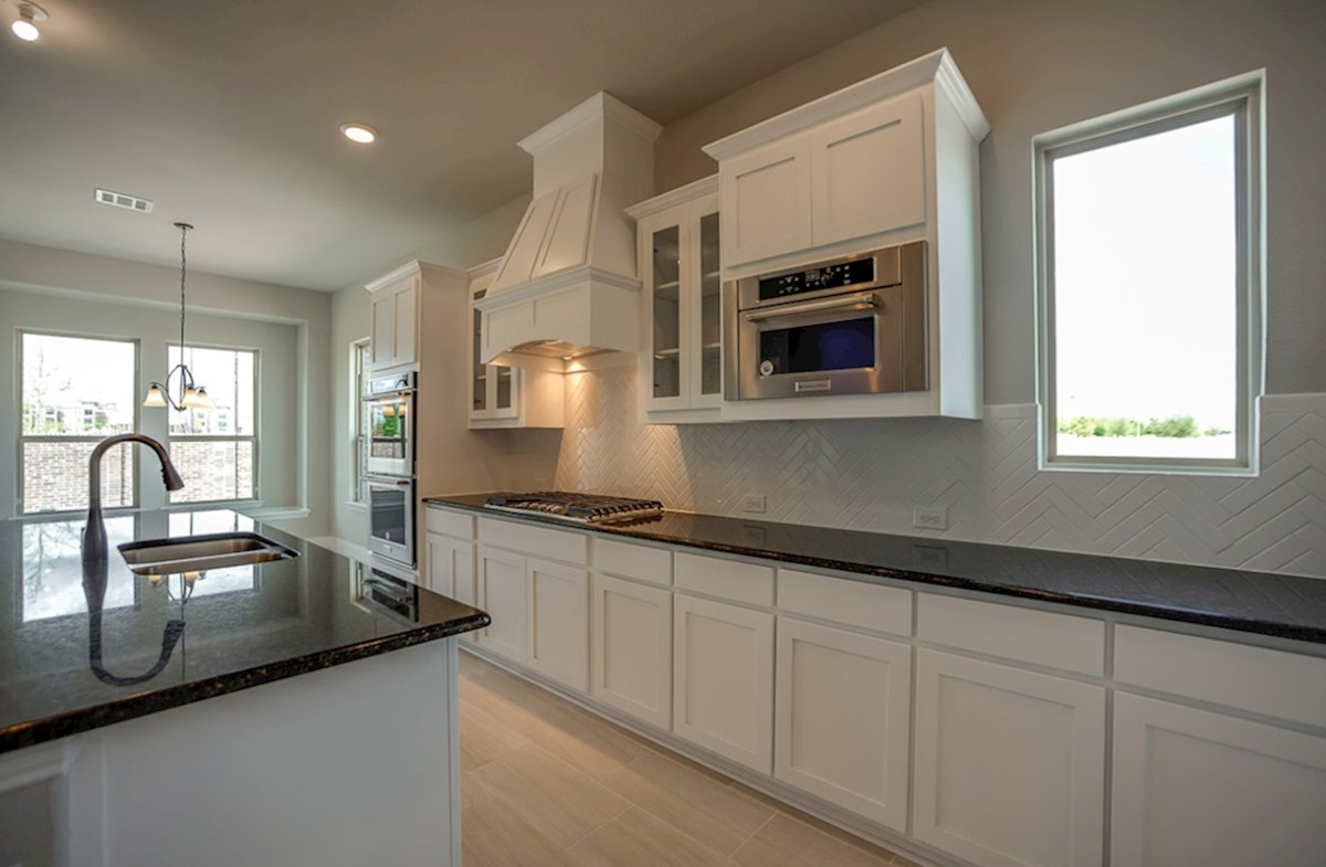 Summerfield quick move-in kitchen with white cabinets and granite countertops