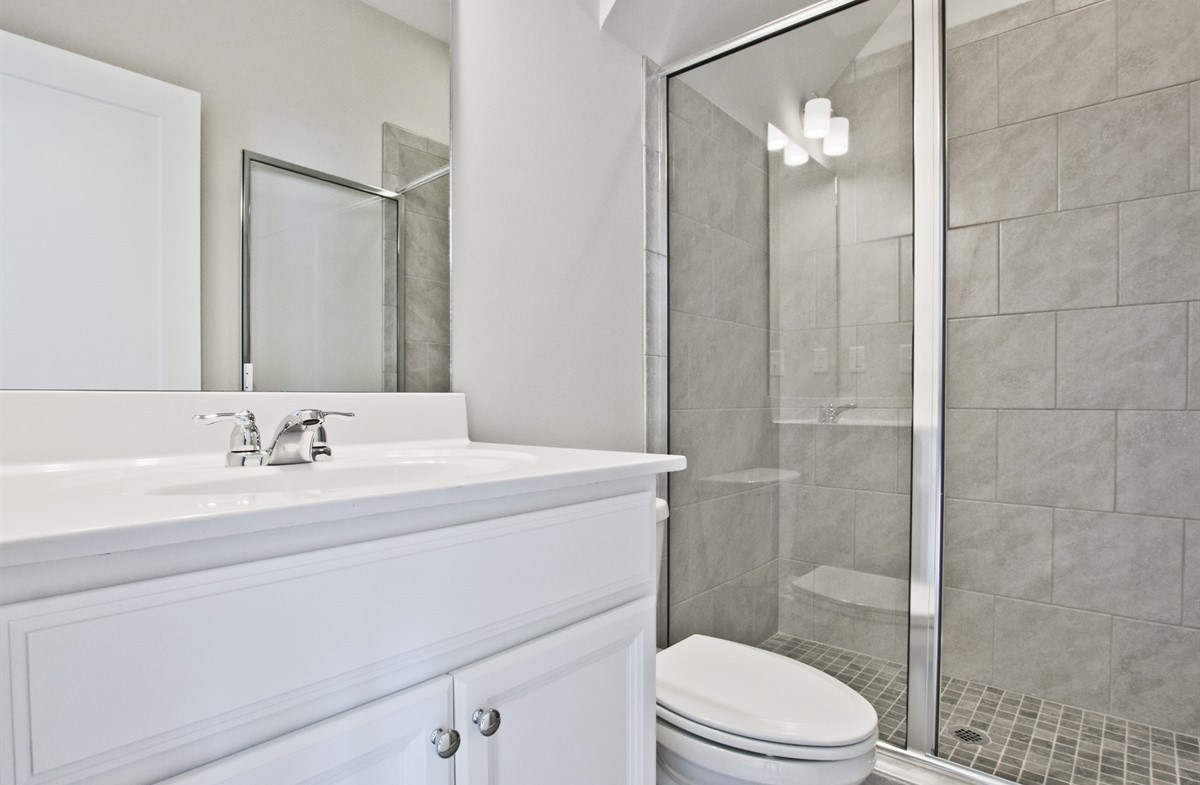 Callahan II quick move-in Secondary Bathroom with white cabinets
