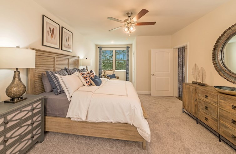Clifton light filled master bedroom with ceiling fan and plush carpet flooring