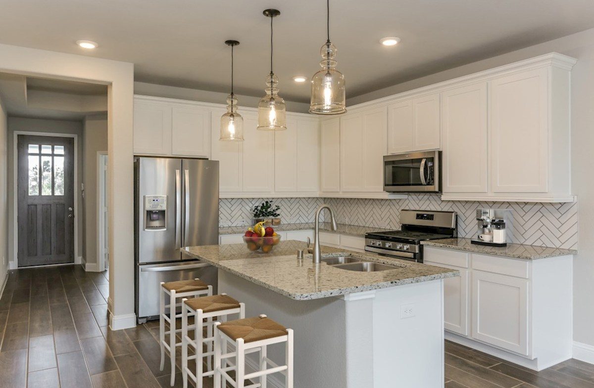 Bridgeland: Harmony Grove Woodrose kitchen with granite countertops, pendant lighting and tile flooring