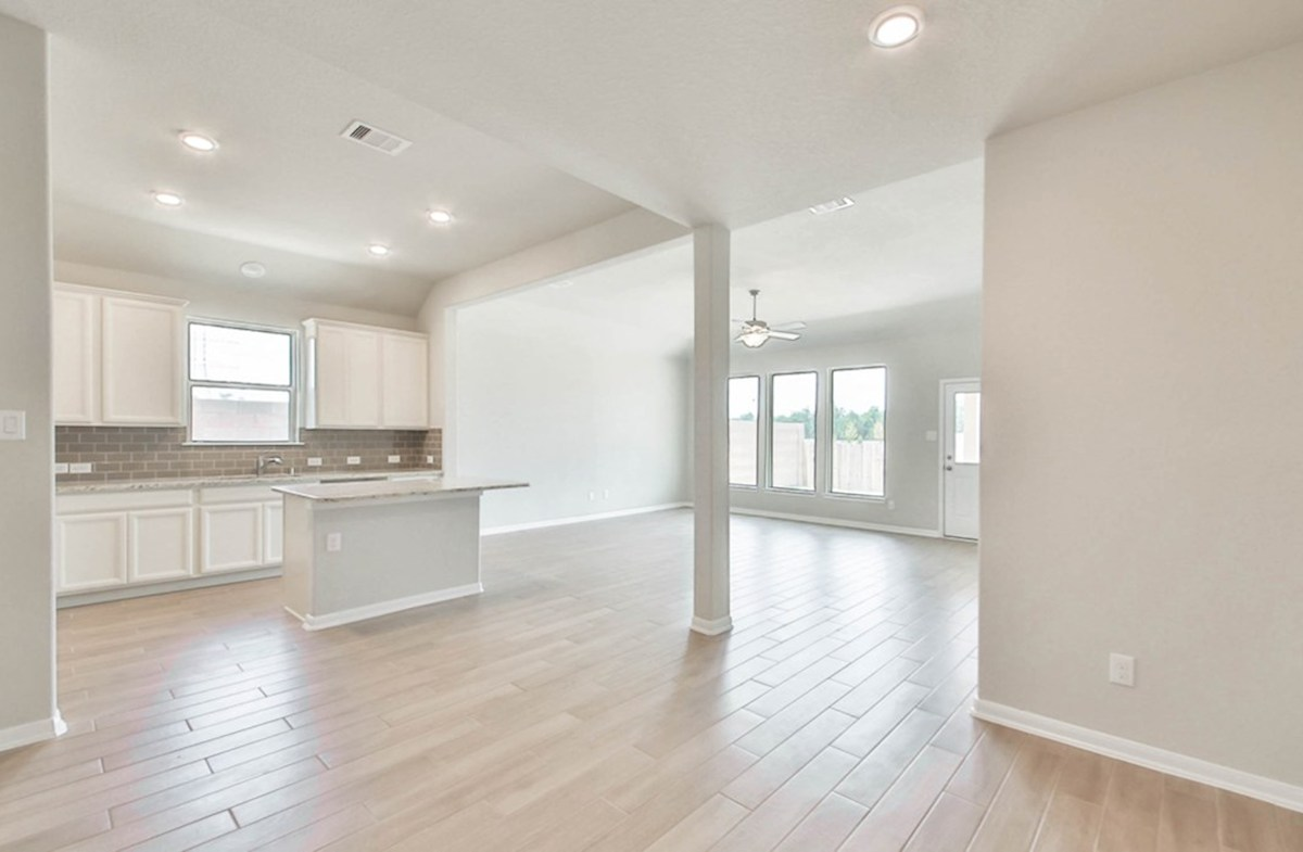 Maxwell quick move-in Great room with tile flooring and ceiling fan that is open to the kitchen and dining area