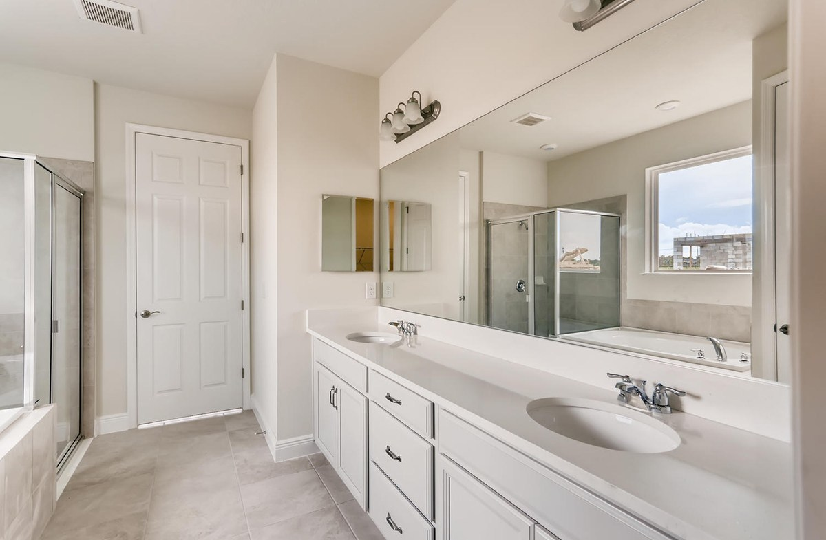 Reserve at Citrus Park Estero Spa-inspired master bathroom with walk-in shower and dual vanity