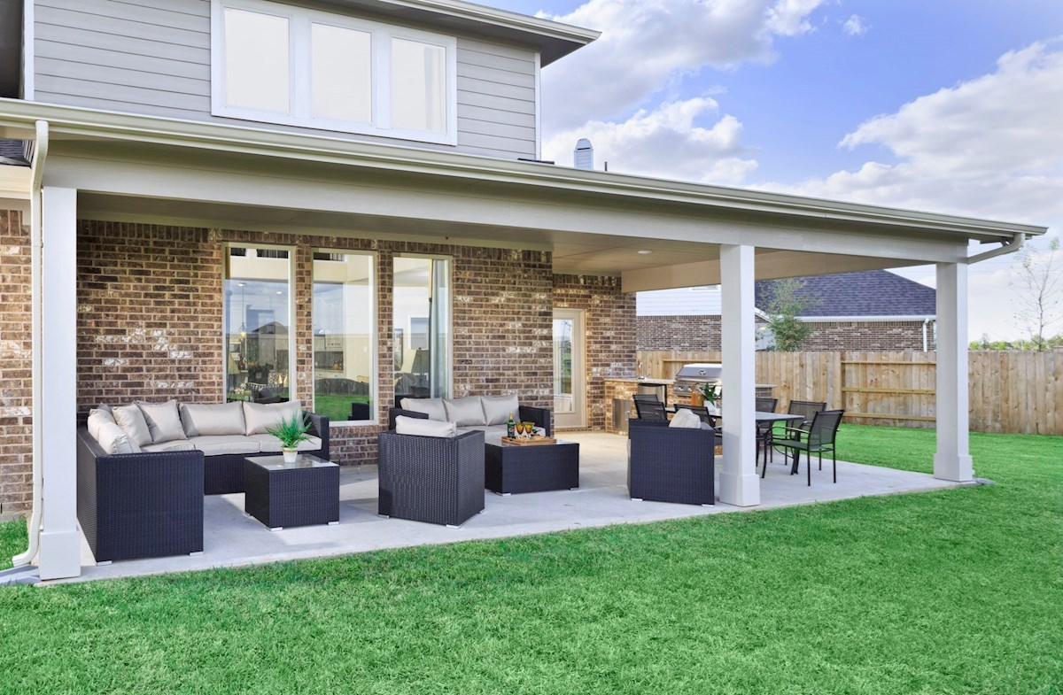 spacious covered patio and lush backyard