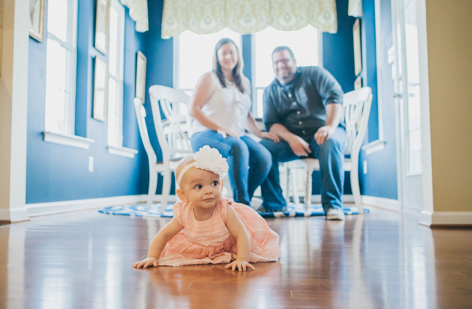 A baby girl crawling on the floor of a new home