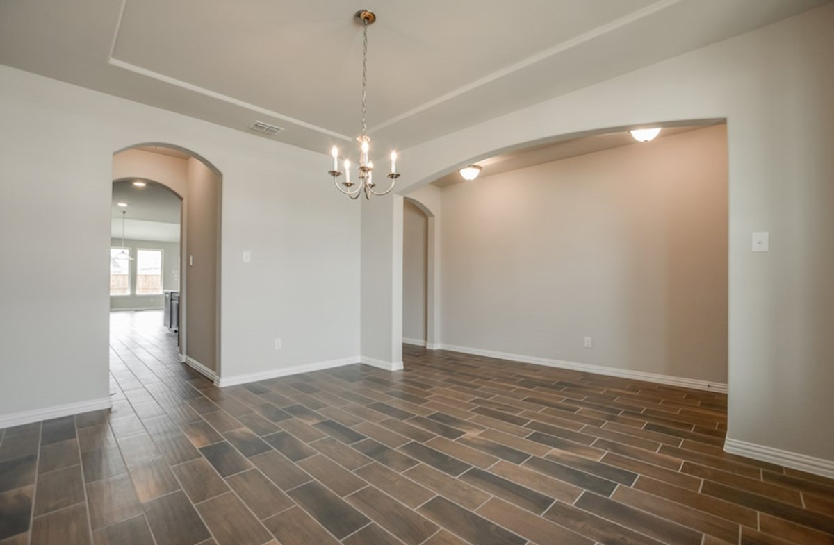 Prescott quick move-in open dining room with tray ceiling and arch entrance