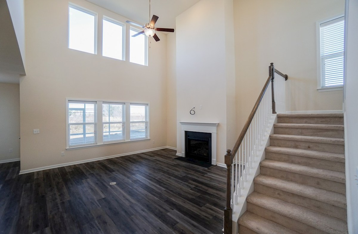 Ivey quick move-in great room features a fireplace and second story windows