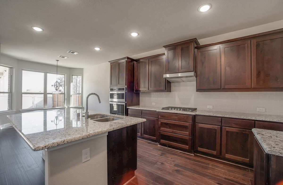Aberdeen quick move-in open kitchen with wood floors and dark cabinets
