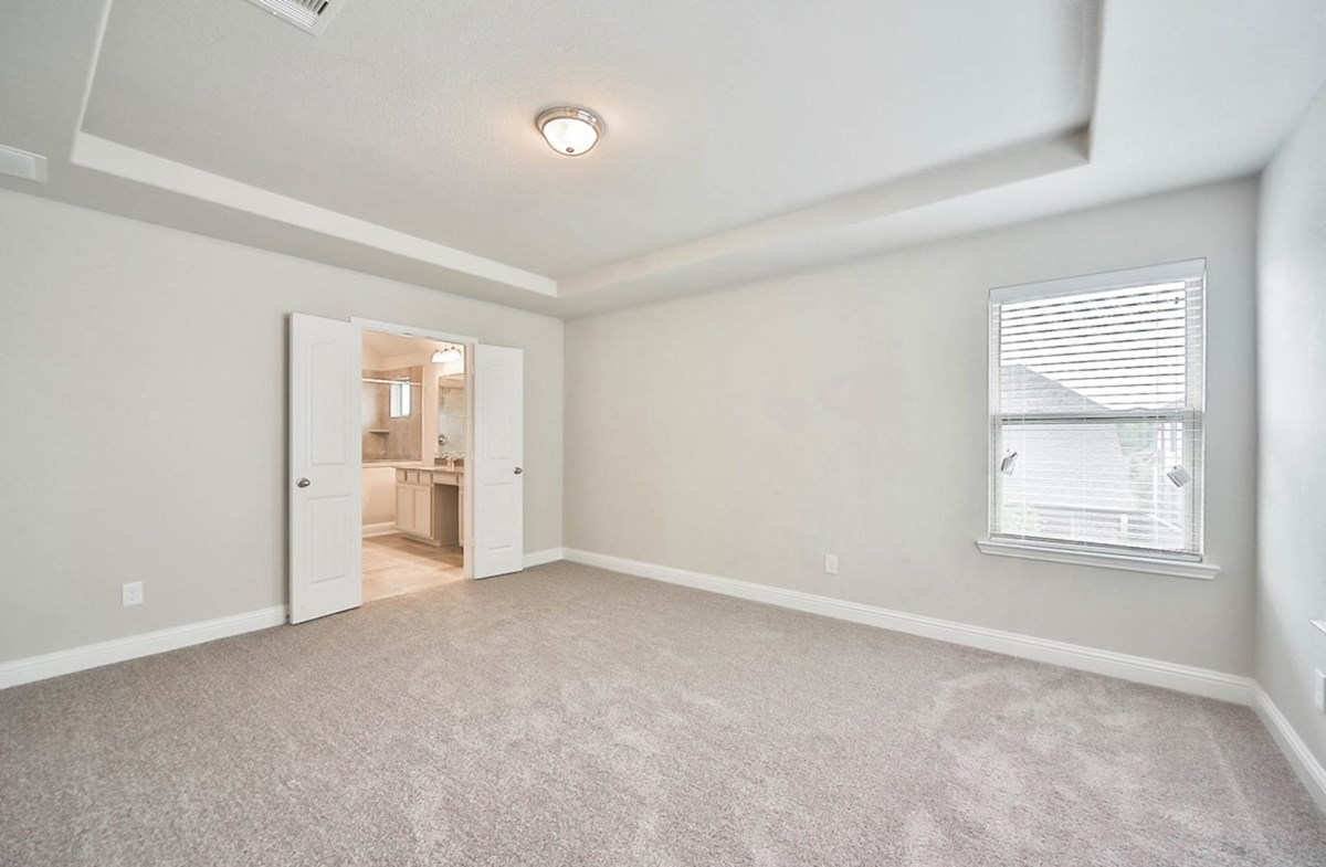 Juniper quick move-in master bedroom with tray ceinling and carpet flooring