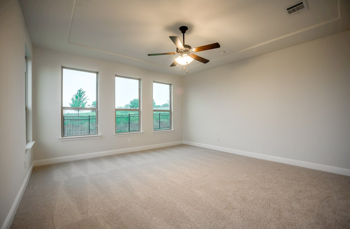 Trinity quick move-in master bedroom with large windows and tray ceiling