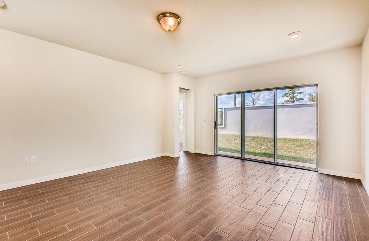 Redington quick move-in Great room with wood-look tile and 3-panel sliding glass door
