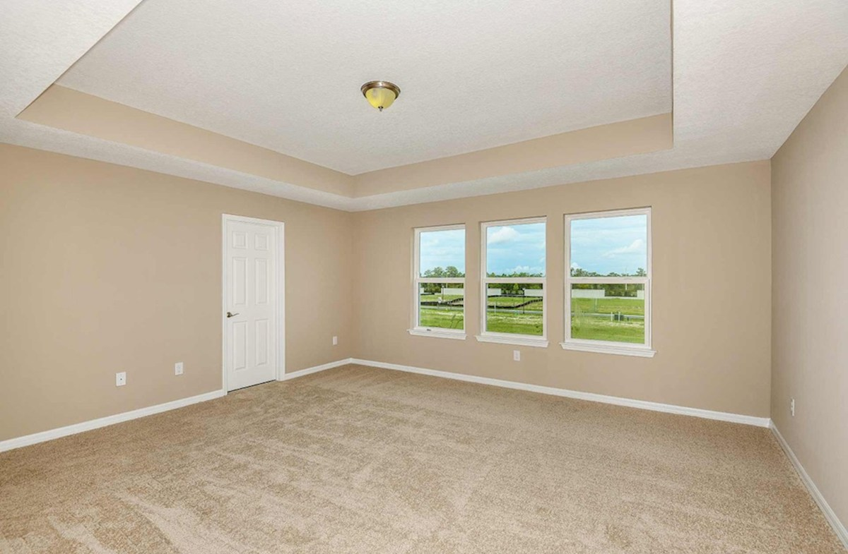 Seagrass quick move-in Master bedroom with a tray ceiling and large windows