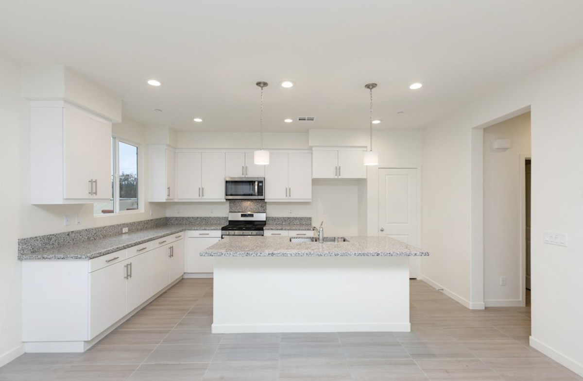 Mission Lane Pinyon Granite countertops and center island with sink provide the ideal location for food preparation