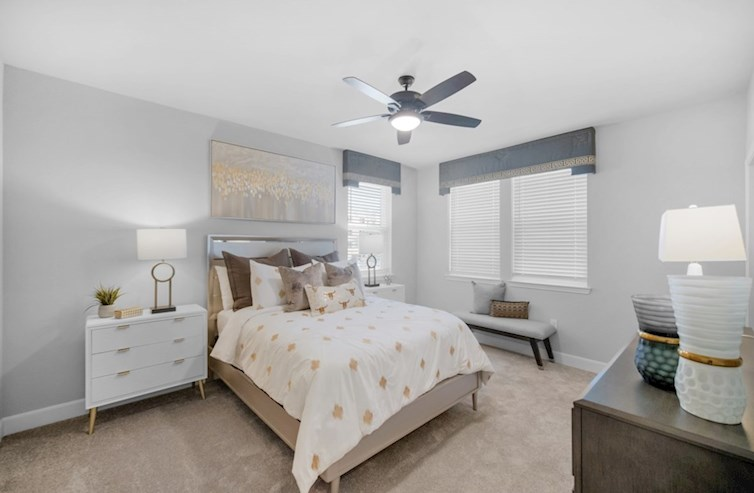 Wiltshire secondary bedroom with carpet floors and ceiling fan