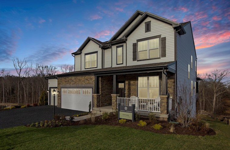 home at dusk with white siding and brown stone