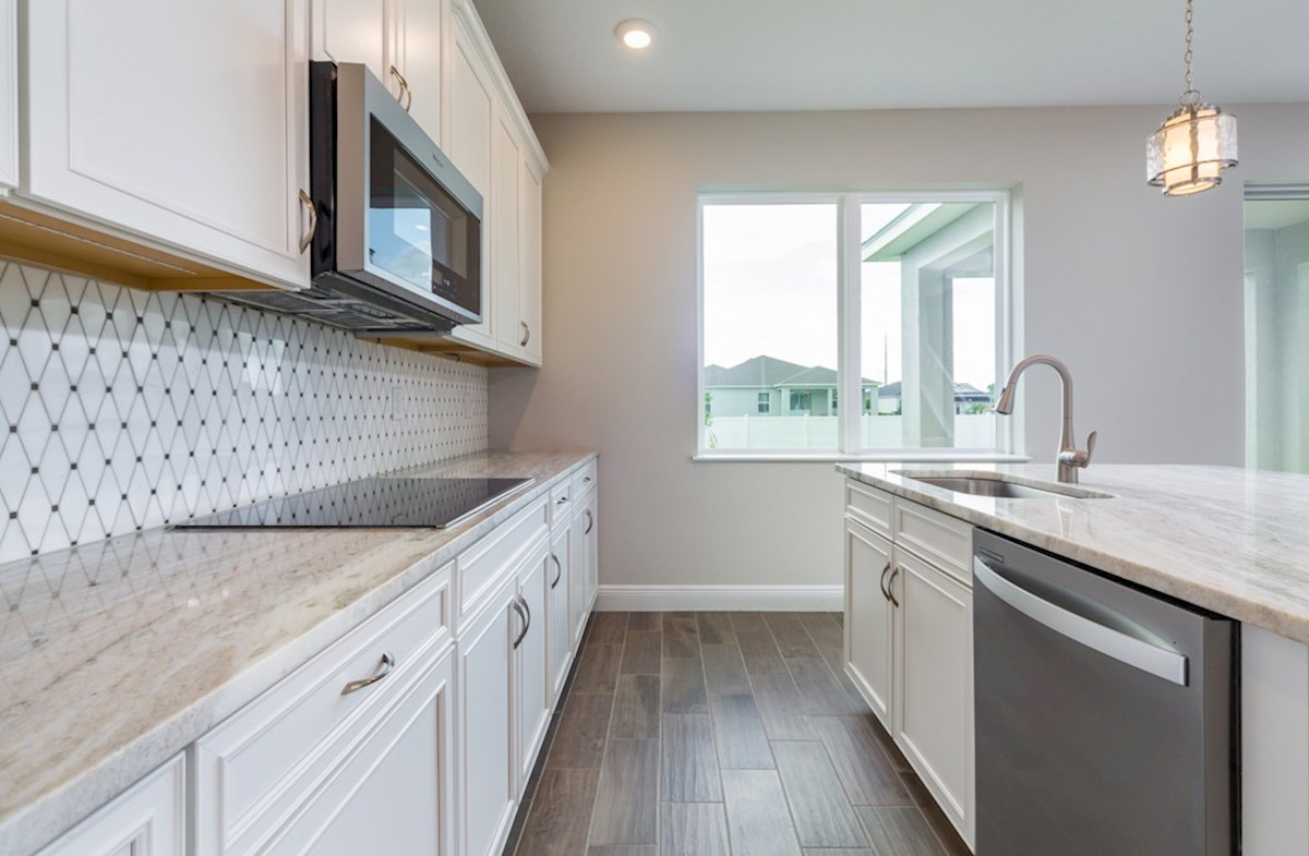 Sand Dollar quick move-in Kitchen with tiled back splash, white cabinets and granite counters