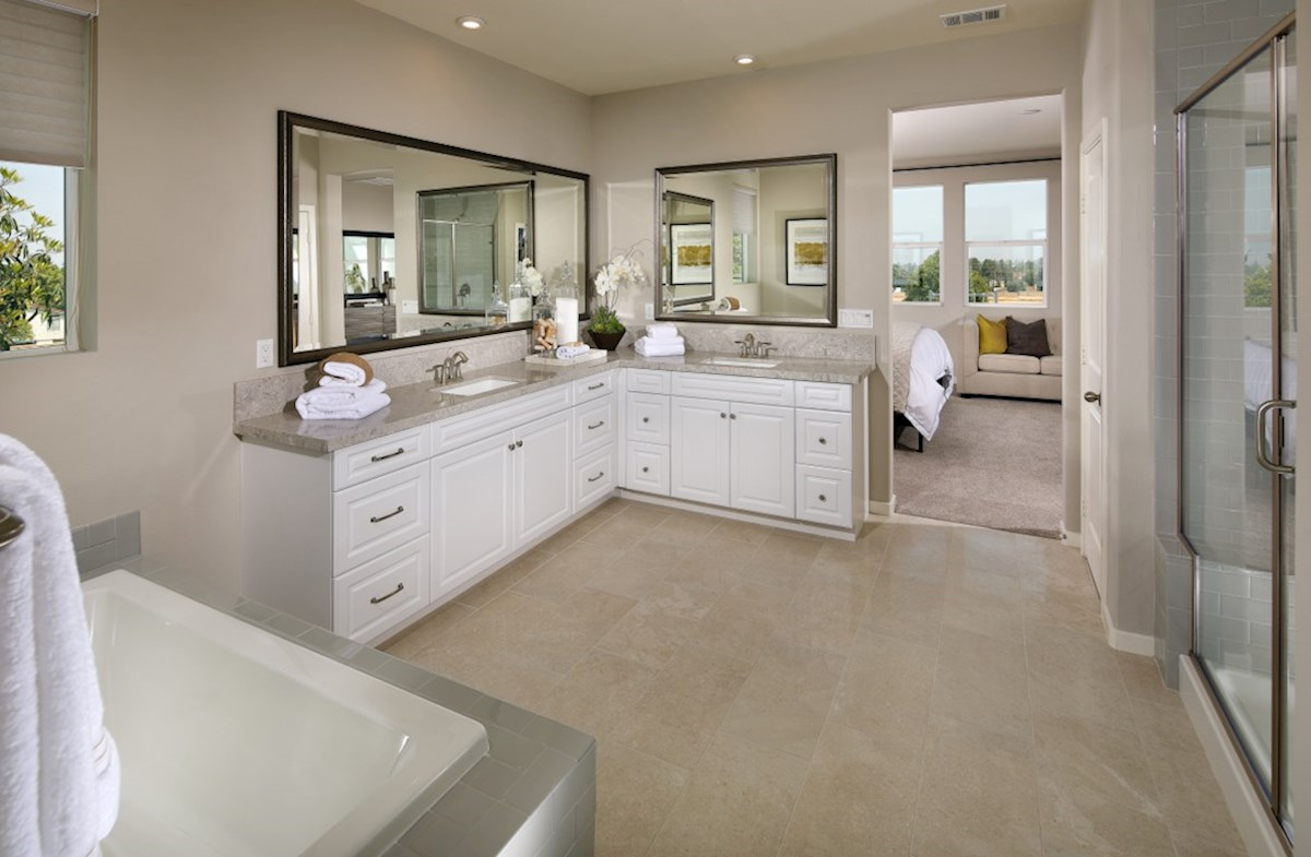 Solstice Indigo Master bath features separate vanities, a spacious walk-in closet, and a spa-inspired soaking tub