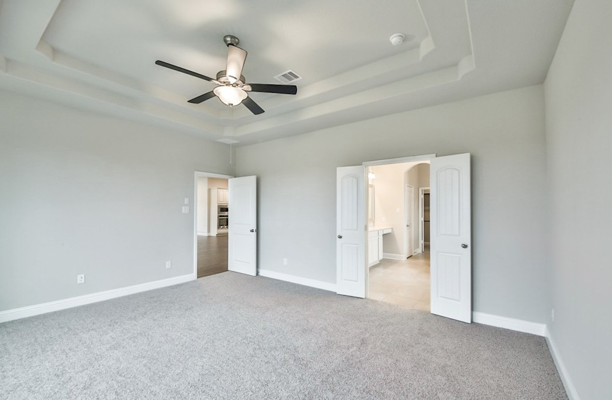 Fredericksburg quick move-in master bedroom with carpet and tray ceilings