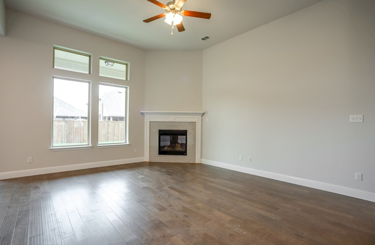 Blakely quick move-in great room with fireplace with large windows and ceiling fan