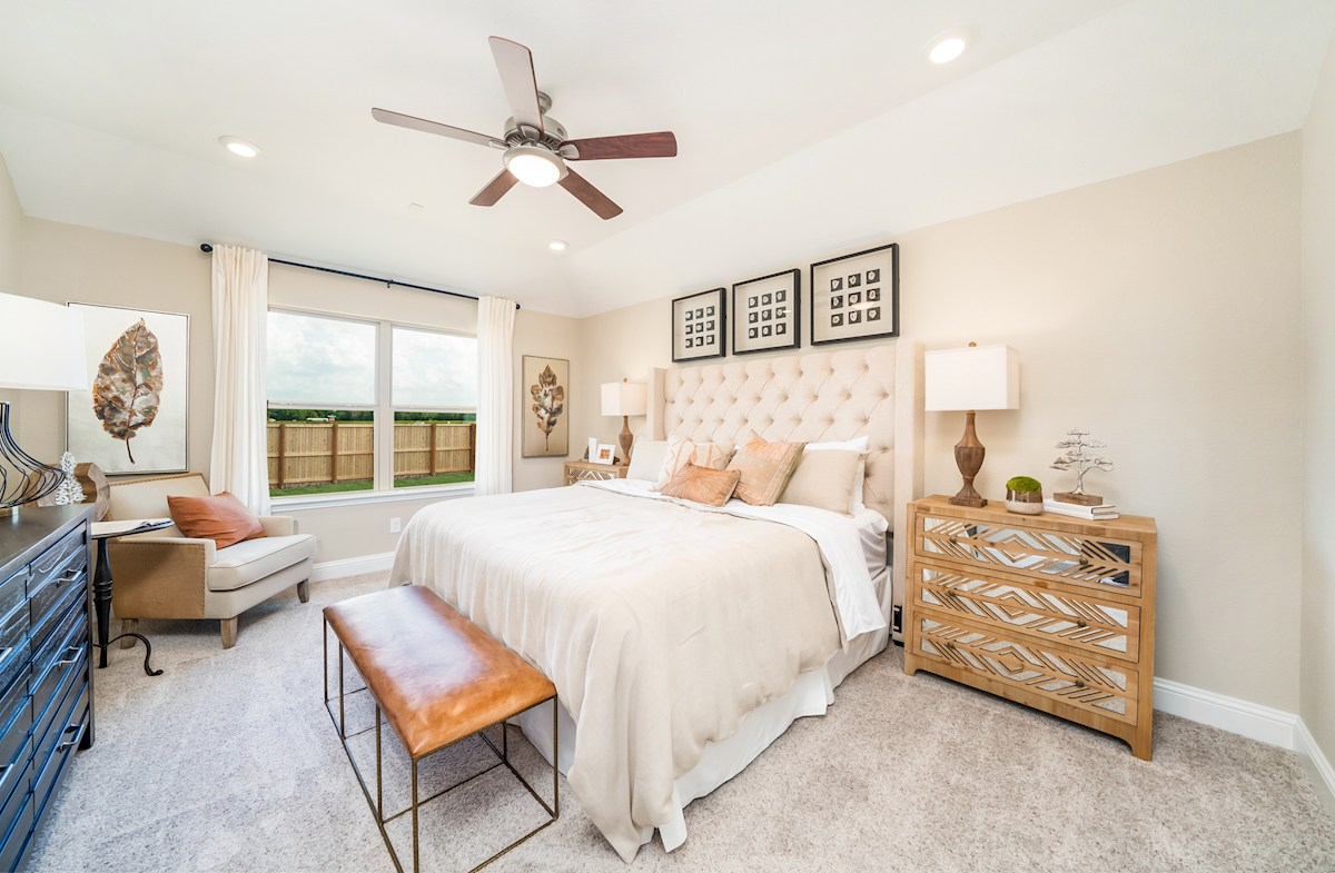 master bedroom with ceiling fan and carpet floors