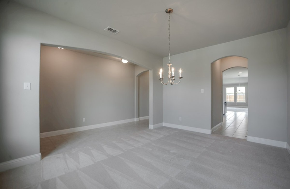 Prescott quick move-in dining room with open arch entrance and carpet