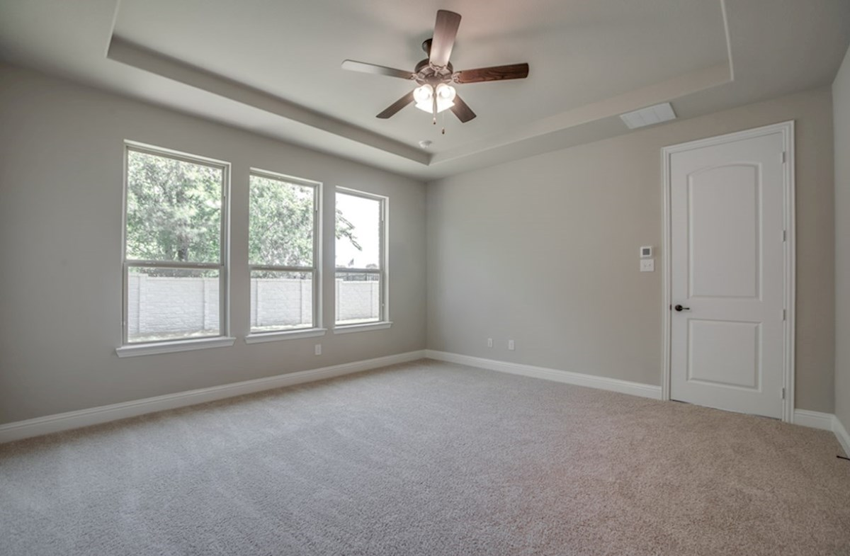 Summerfield quick move-in master bedroom with carpet and ceiling fan