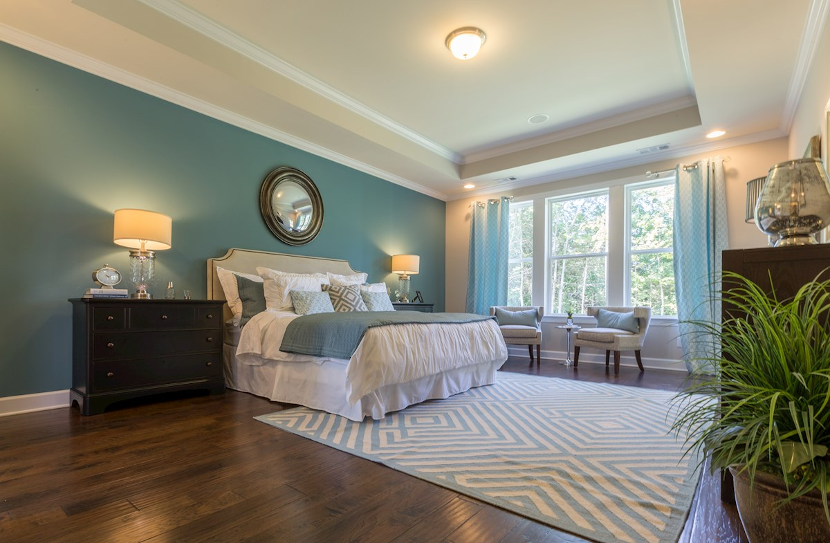 turquoise master bedroom with triple windows