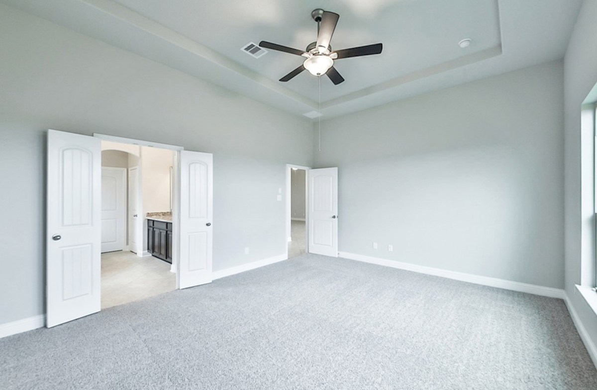 Galveston quick move-in master bedroom with carpet flooring and tray ceiling