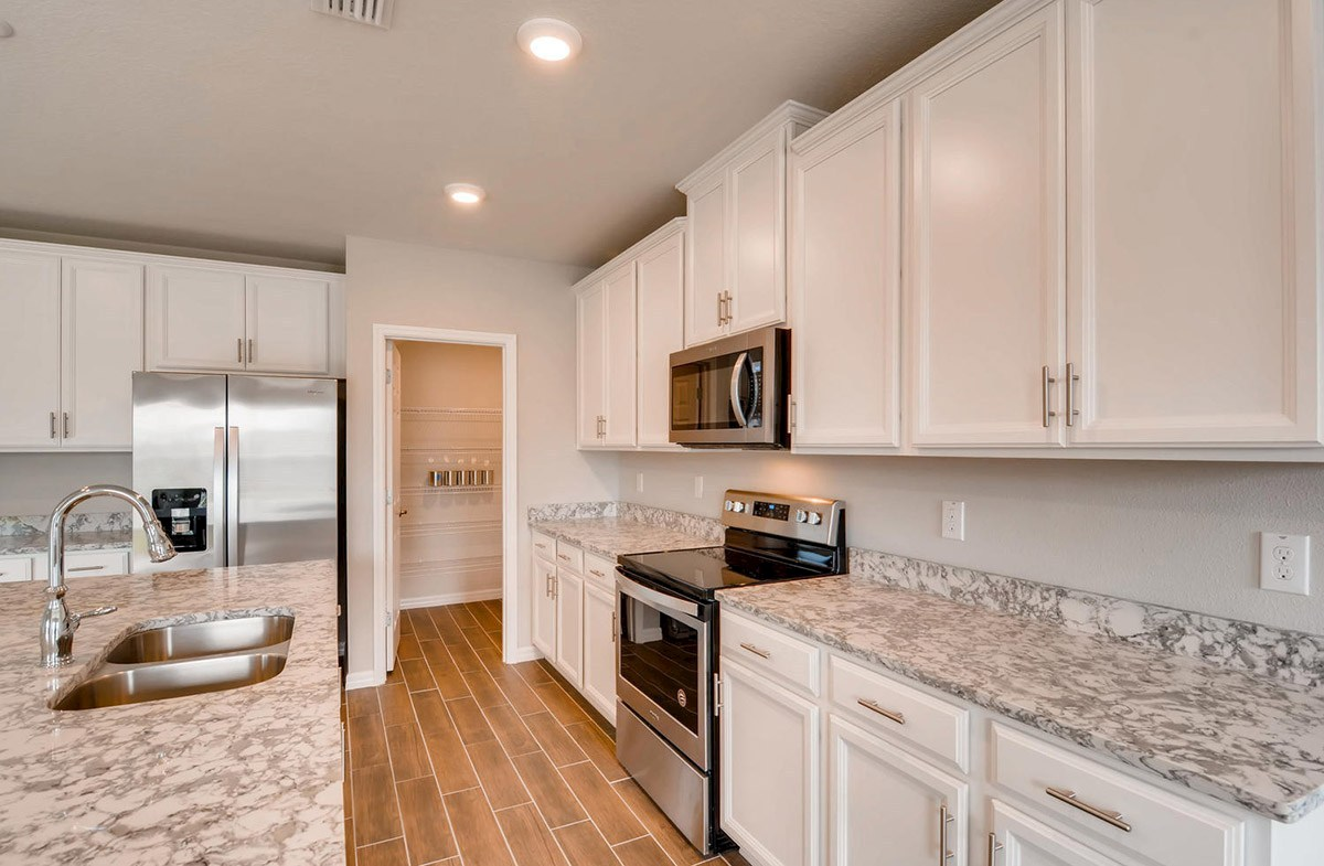 Cypress Pointe quick move-in Kitchen with white cabinets and stainless steel appliances