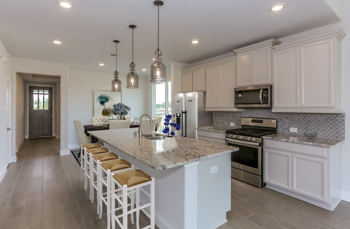 Bridgeland: Harmony Grove Spicewood kitchen with granite countertops and white cabinetry