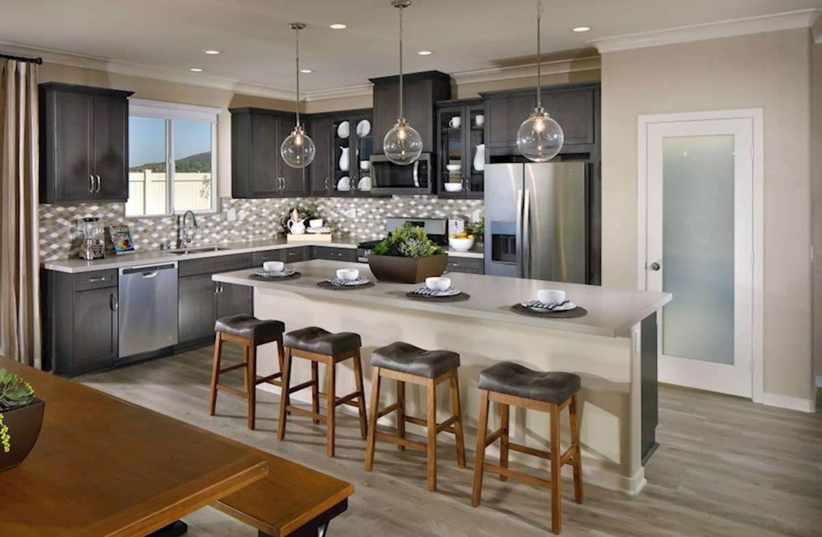 Provence at Heritage Ranch Piedmont Granite countertops and center island with sink provide the ideal location for food preparation.