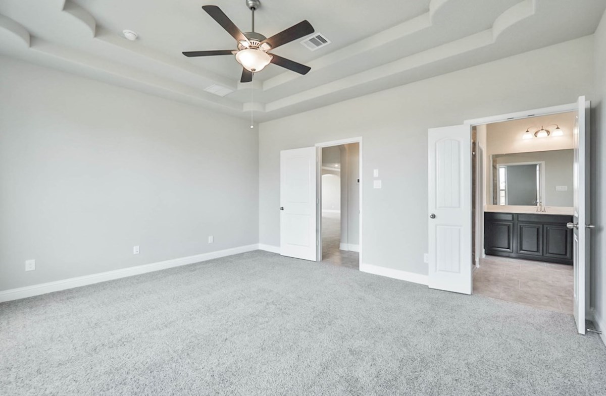 Harper quick move-in master bedroom with tray ceiling and carpet floors