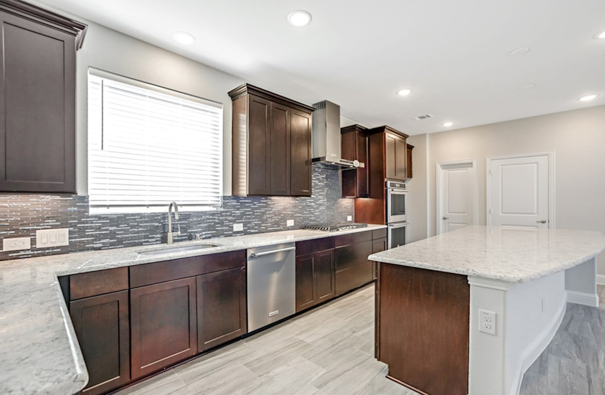Hamilton quick move-in open kitchen with dark cabinets that opens to great room